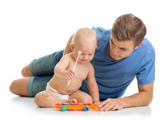Father and baby boy having fun with musical toys. Isolated on wh
