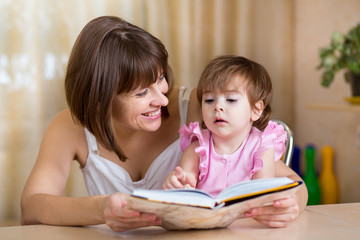 mother and kid daughter read a book