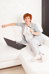 Mature woman with credit card and laptop