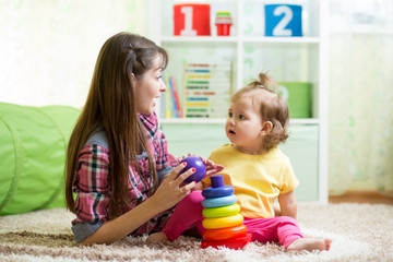 cute mother and kid girl playing together indoor at home