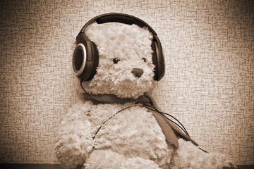 Teddy bear listening to music on headphones. sepia toned