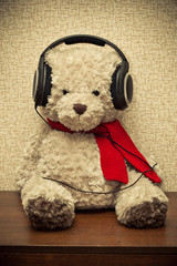 retro bear listening to music on headphones. photo toned yellow
