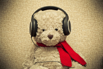 retro bear listening to music on headphones. photo toned yellow