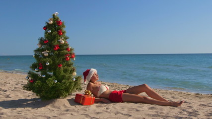 Girl in Santa hat enjoying Christmas vacation time on beach