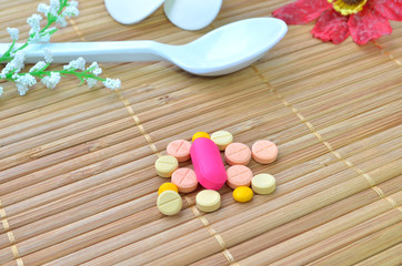 many colorful medicine tablet and spoon with flower