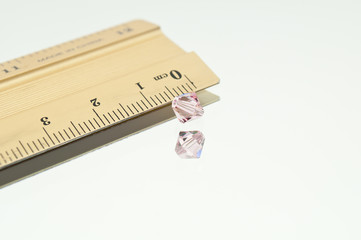 Pink Swarovski Double Cone Besides Ruler