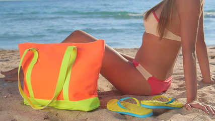 Bikini girl with colorful accessories on sandy beach