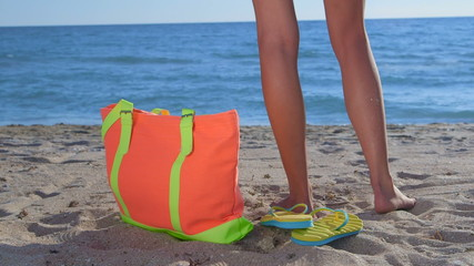 Colorful bag and flip-flops on sandy beach bikini woman