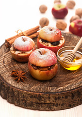 Baked apples with honey, raisins and nuts on wooden board