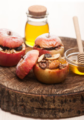 Baked apples with honey, raisins and nuts on wooden background