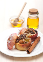 Baked apples with honey, raisins and nuts on light background