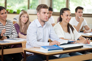Male student listening  a lecture in classroom