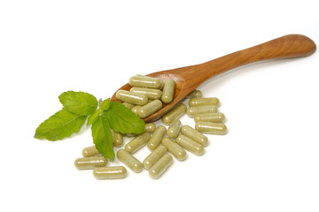 Herbal drug capsules inwooden spoon . Alternative medicine conce