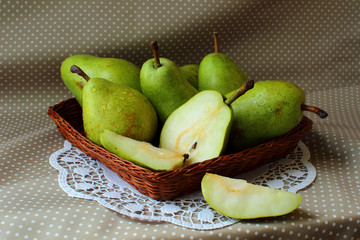 Green pears in a basket and one of them cut into the share.