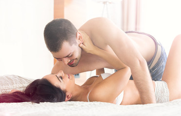 Sexy young couple lying on bed