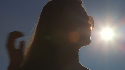 Woman face in sunglasses against the sun