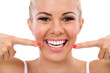 Smiling woman pointing in her perfect teeth