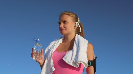 Athletic girl drinks water after running and exercising outdoors