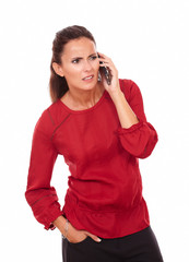 Confused hispanic lady talking on her phone