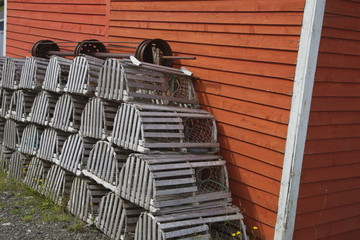 Lobster traps against red house