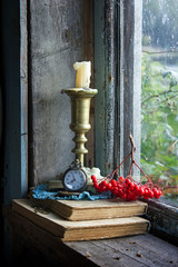 Old books, clocks and candle on a windowsill