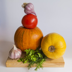 Pumpkin, tomatoes, garlic and greens on a table