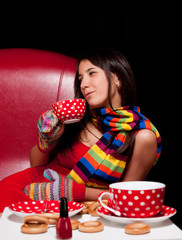 brunette girl sitting on the chair with a cup of peas in hand