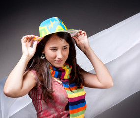 smiling brunette in bright hat and colorful striped scarf