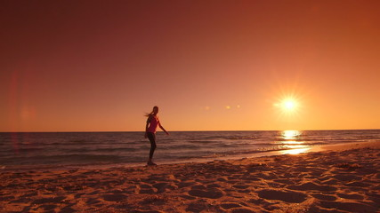 Fitness sporty woman jogging along the beach at sunset
