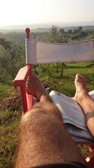 Männerbeine auf rot-weißem Klappstuhl