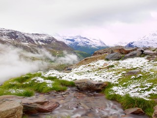 First snow in Alps touristic region. Green meadow with stream.