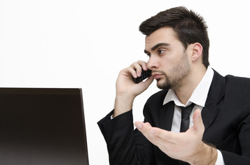 Businessman on the phone troubleshooting in front of laptop