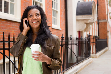 beautiful woman walking down the street talking on the phone.