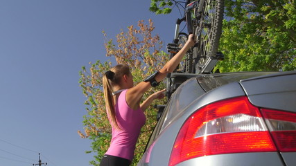 Sporty young woman takes down bicycle from roof of his car