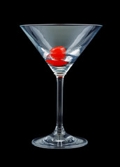 An empty cocktail glass with a maraschino cherry