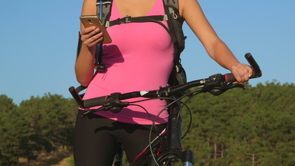 Active woman cyclist on bicycle using smart phone  cycling