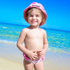 Bambina al mare con cappello rosa