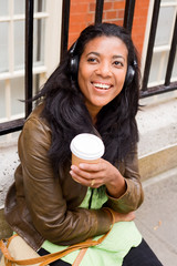 young woman enjoying coffee and music.