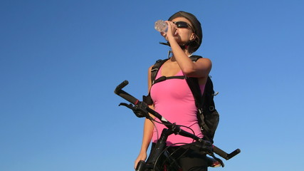 Young woman cyclist on mountain bike drinking water