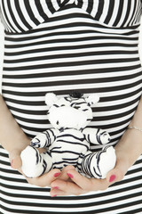 Belly of pregnant woman in stripped dress with zebra toy