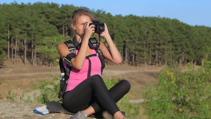 Hiking young woman taking pictures during hike trekking
