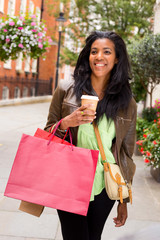 young woman with shopping bags and a take away coffee