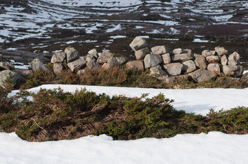 Snow covering the ground and stone wall
