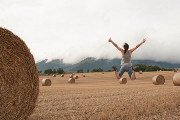Young woman jumping in a harvested cereal field