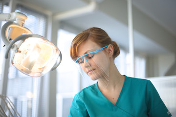 Portrait of beautiful dentist closed eyes with switched lamp