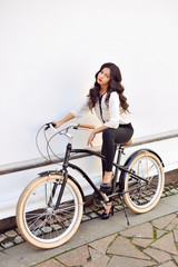 Fashionable young woman on bicycle