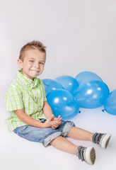 Smiley little boy with blue balloons