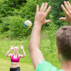 Young couple playing volleyball in park.