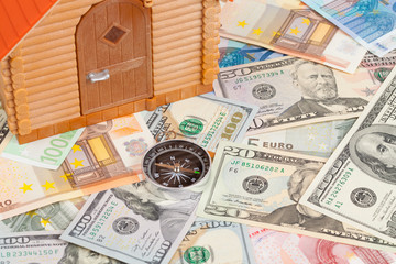 Plastic house on a pile of money