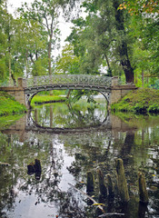 Picturesque landscape with old bridge over flow in the park